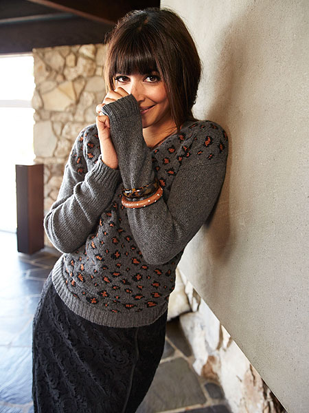 Black sweater with white shirt collar and striped crossbody bag on New Girl.
